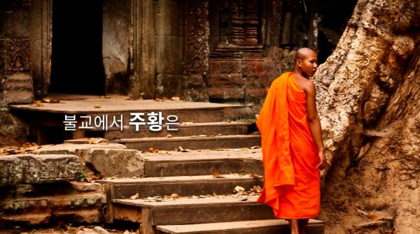 주황색 승려복을 입고있는 승려, 승려 왼쪽에 글 '불교에서 주황은'