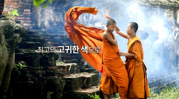 주황색 승려복을 입고있는 두명의 승려, 승려 왼쪽에 글 '최고의 고귀한 색으로'