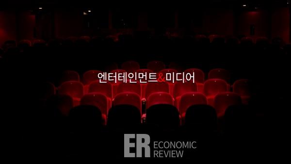 극장 관람석 한 가운데 켜진 조명, 조명 빛 받은 빨간색 의자 위에 글 '엔터테인먼트&미디어'
